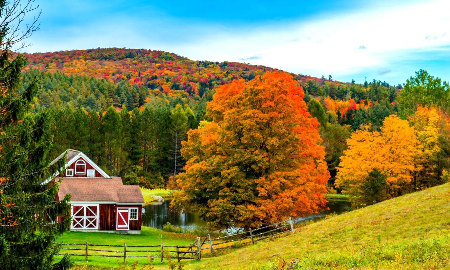 Photograph of an American autumn landscape. Red barn nestled in red, orange and green-leafed trees.